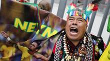 A Peruvian shaman performs a ritual while holding a poster of Brazil's soccer player Neymar outside the National Stadium in Lima, June 10, 2014. The shaman is blessing the 2014 World Cup host nation Brazil and key soccer players good luck. (Enrique Castro-Mendivil/REUTERS)