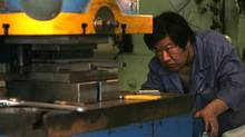 A Chinese worker operates a machine at a metal factory in Beijing