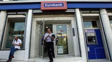 A man comes out of an Eurobank branch in central Athens Oct. 5, 2012. (JOHN KOLESIDIS/REUTERS)