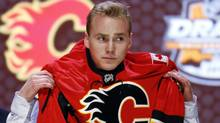 Samuel Bennett pulls on a Calgary Flames sweater after being chosen fourth overall during the first round of the NHL hockey draft, Friday, June 27, 2014, in Philadelphia. (Associated Press)