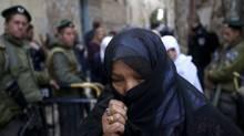 A Palestinian woman passes by Israeli border policemen on guard in Jerusalem's Old City in March. (MENAHEM KAHANA/MENAHEM KAHANA/AFP/Getty Images)