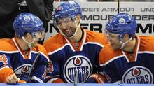 Edmonton Oilers' Sam Gagner (C) talks with linemates Jordan Eberle (L) and Taylor Hall on the bench after scoring his fourth goal against the Chicago Blackhawks during the third period of their NHL hockey game in Edmonton. (DAN RIEDLHUBER/Reuters)