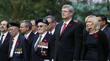Prime Minister Stephen Harper, second right, accompanied by his wife Laureen, right, Canadian veterans and officials, attends at a Remembrance Day ceremony at Sai Wan War Cemetery in Hong Kong Sunday, Nov. 11, 2012. The ceremony honored the 1,975 Canadian soldiers who fought to defend Hong Kong during the WWII and remembered over 550 Canadian soldiers who died in the battle. (Kin Cheung/AP)