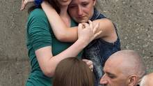 People comfort each other in front of the refugee centre at the local high school Sunday, July 7, 2013 in Lac-Mégantic, Quebec after a train derailed ignited tanker cars carrying crude oil. A year later, the deadly train disaster still haunts the people of Lac-Megantic. (Ryan Remiorz/THE CANADIAN PRESS)