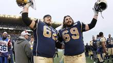 Winnipeg Blue Bombers' Steve Morley (62) and Glenn January (69) wave good bye to the fans after defeating Montreal Alouettes in their final CFL game at Canad Inns Stadium in Winnipeg Saturday, November 3, 2012. (John Woods/THE CANADIAN PRESS)