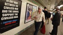 "Cyrus McGoldrick, a member of the Council on American-Islamic Relations, talks to commuters as they walk by an advertisement that reads ""Support Israel/Defeat Jihad"" in the Times Square subway station in New York, September 24, 2012. (BRENDAN MCDERMID/REUTERS)"