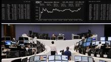 Traders are pictured at their desks in front of the DAX board at the Frankfurt stock exchange September 3, 2012. (Lizza May David/REUTERS)