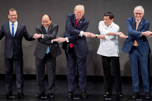Nov. 13, 2017: Mr. Trump, middle, joins hands with world leaders for a group photo at the opening ceremony of the ASEAN summit in Manila. So far, Mr. Trump's counterparts abroad have found ways to restrain Mr. Trump's impulses, or to carry on despite them.