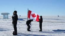 People take part in a memorial ceremony for the Kenn Borek aircrew who died in last week's crash in Antarctica, at the National Science Foundation's Amundsen-Scott South Pole Station on Monday, Jan. 28, 2013. (Blaise Kuo Tiong/THE CANADIAN PRESS)