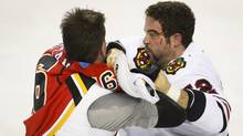 Chicago Blackhawks' Brandon Bollig, left, fights with Calgary Flames' Brian Mcgrattan during first period NHL hockey action in Calgary, Alta., Wednesday, Nov. 27, 2013. (JEFF MCINTOSH/THE CANADIAN PRESS)