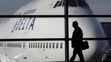 A passenger walks past a Delta Airlines 747 aircraft in McNamara Terminal at Detroit Metropolitan Wayne County Airport in Romulus, Mich. (PAUL SANCYA/ASSOCIATED PRESS)