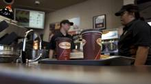 Employees prepare an order at a Tim Hortons Inc. restaurant in Oakville, Ont. (Brent Lewin/Bloomberg)