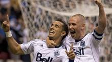 Vancouver Whitecaps FC Camilo Sanvezzo, left, celebrates his goal with teammate Kenny Miller during the first half against Chivas USA during first half of MLS action in Vancouver, Wednesday, June, 19, 2013. (JONATHAN HAYWARD/THE CANADIAN PRESS)