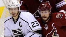 Los Angeles Kings right wing Dustin Brown (23) is checked by Phoenix Coyotes rig