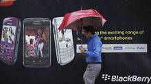 A man tries to hold on to his umbrella as he walks past a Blackberry advertisement billboard in Mumbai. (DANISH SIDDIQUI/REUTERS)