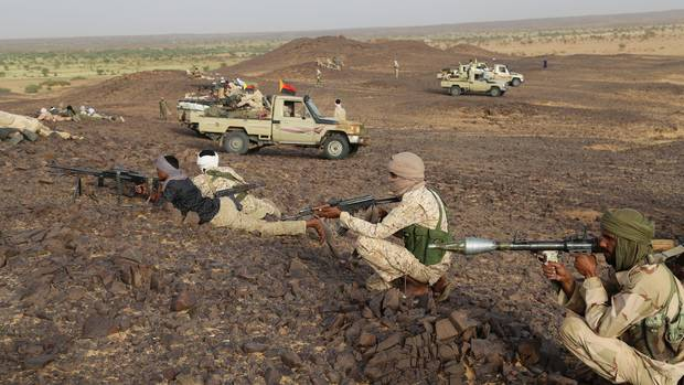 Tuareg fighters stand with weapons near Kidal, northern Mali, on Sept. 28.