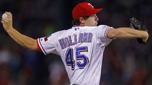 Texas Rangers starting pitcher Derek Holland pitches to the St. Louis Cardinals during the first inning in Game 4 of MLB's World Series baseball championship in Arlington, Texas, October 23, 2011.    (Reuters)