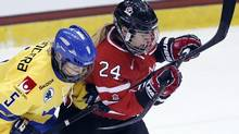 Sweden's Johanna Fallman (5) ties up Canada's Natalie Spooner (24) in front of the net during the first period of a Four Nations Cup women's hockey game on Friday, Nov. 8, 2013, in Lake Placid, N.Y. (MIKE GROLL/AP)