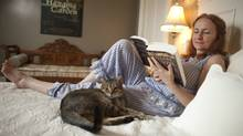 Stratford actor Seana McKenna reads in bed at her home in Harrington, Ontario. (GEOFF ROBINS FOR THE GLOBE AND MAIL)