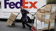 A FedEx driver carts packages in New York in this file photo. (Mark Lennihan/AP)