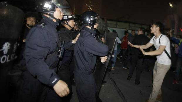 Chinese anti-riot police force protesters to leave the area outside the city government office in Zhejiang province's Ningbo city, Oct. 28, 2012, during a protest against the proposed expansion of a petrochemical factory. China's increasingly affluent urban population is becoming more aware of environmental issues. (Ng Han Guan/AP)