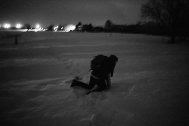 An exhausted asylum seeker, bogged down by heavy snow, crosses the Canadian border in Noyes.
