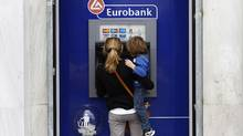 A woman makes a transaction at an ATM machine outside a Eurobank branch in Athens. That Greece is hurtling towards the euro zone's exits has been accepted, and apparently fully discounted, by the markets. Far more worrisome is the rapid deterioration of the Spanish economy and its banking system (JOHN KOLESIDIS/REUTERS)