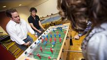Capital One Canada president Rob Livingston, left, gets in a game of foosball with employees at their Toronto offices Wednesday. (Tim Fraser for The Globe and Mail/Tim Fraser for The Globe and Mail)