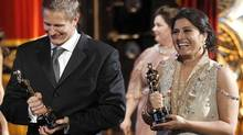 "Sharmeen Obaid-Chinoy (right) and Daniel Jung leave the stage after accepting the Oscar for best documentary short for ""Saving Face"" at the 84th Academy Awards on Sunday. (Chris Carlson/AP)"