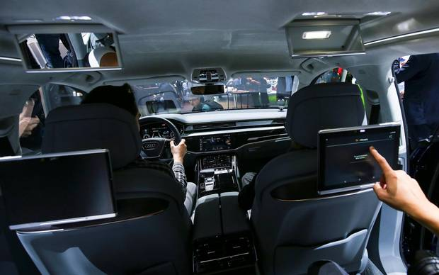 Attendees view the rear seat of the Audi A8 at the Audi Summit.