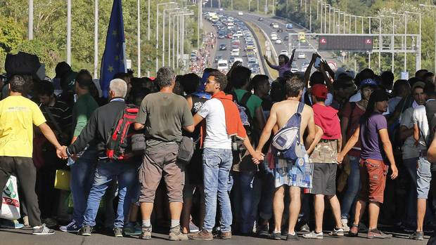 Migrants hold hands as they walk out of Budapest, Hungary, on Sept. 4, 2015.