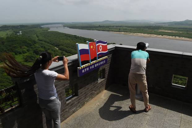 Visitors look out toward Russia, left, and North Korea, right, at the viewing tower in Hunchun.