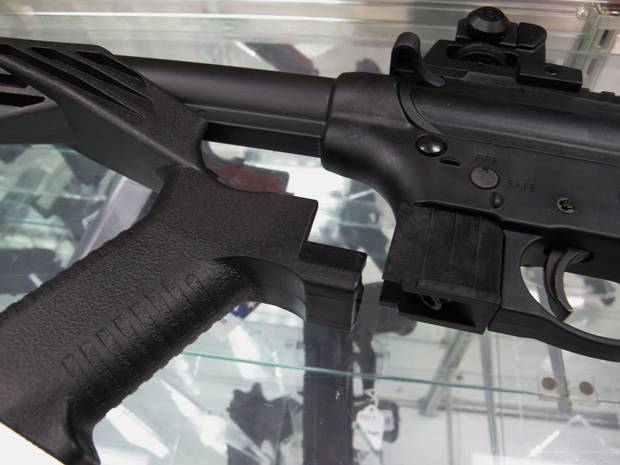 The bump stock, shown at left next to a disassembled rifle.