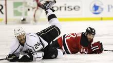 Los Angeles Kings' Colin Fraser, left, hits the ice after colliding with New Jersey Devils' Stephen Gionta in the second period during Game 5 of the NHL hockey Stanley Cup finals, Saturday, June 9, 2012, in Ne