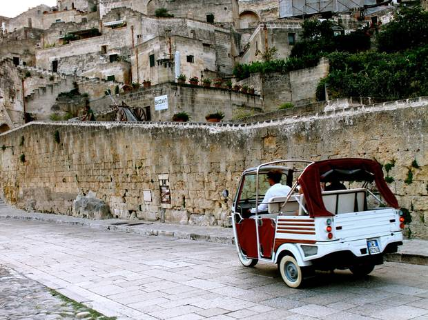 Tour guides drive tourists around Matera in adorable vintage Ape cars.