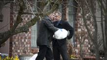 A member of the B.C. Coroners Service carries a bag with the body of a dead infant which was found in a plastic bag between two houses in East Vancouver March 31, 2009. (John Lehmann/The Globe and Mail)