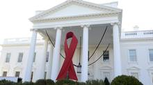 A giant red ribbon hangs from the North Portico of the White House to mark World AIDS Day, December 1, 2013, in Washington. (MIKE THEILER/REUTERS)