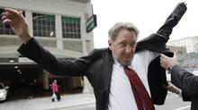 Oracle CEO Larry Ellison, left, puts on his suit as arrives for a court appearance at a federal building in San Francisco, Tuesday, April 17, 2012. (Paul Sakuma/Paul Sakuma/AP)