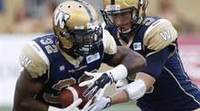 Winnipeg Blue Bombers' quarterback Drew Willy hands off to Nic Grigsby