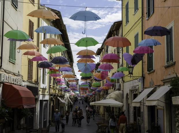 Hundreds of colored flying umbrella colors hang over the Tuscan art town of Pietrasanta.