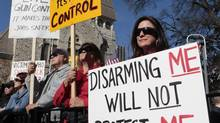 Marylou Harris holds a sign as she listens to speakers during the Guns Across America pro-gun rally at the State Capitol in Atlanta on Jan. 19, 2013. (TAMI CHAPPELL/REUTERS)