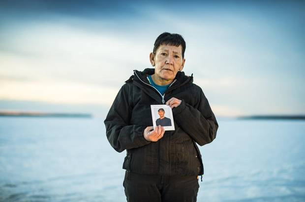 """Rose Montgrand stands on Lac La Loche in La Loche, Saskatchewan January 27, 2016 holding a photo of her son Devin who committed suicide last September. There are times she forgets he is gone. """"I hear someone come in the door and I think it might be him,"""" she said. """"Sometimes, I even say his name."""""""