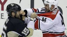 Carolina Hurricanes' Jay Harrison (44) lands a punch in the face of Pittsburgh Penguins' Tanner Glass (15) during a first-period fight in an NHL game in Pittsburgh, Tuesday, Oct. 8, 2013. (Gene J. Puskar/AP)