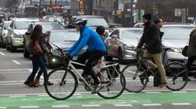 Cyclists using the separated bike lane on Hornby St. ride across West Georgia St. in Vancouver, January 26, 2014. (DARRYL DYCK for THE GLOBE AND MAIL)