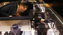 An employee adjusts a display of Mont Blanc jewellery at the luxury-goods company's store in Beijing. (David Gray/REUTERS)