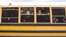 Children looking through windows of bus thinkstock (Jupiterimages/iStockPhoto)