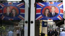 People walk by a cafe in London flying the Union Jack flag with a central picture of Prince William and Kate Middleton, Thursday, April 21, 2011. (Sang Tan/AP)