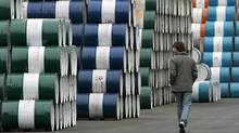 A man walks past storage area for oil barrels in Shanghai. (ALY SONG/Aly Song/Reuters)