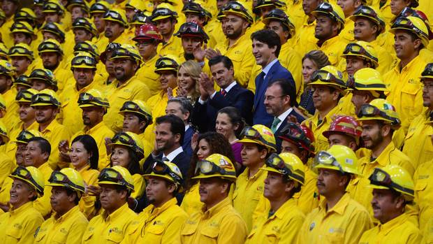 At the news conference, Mr. Trudeau, Mr. Pena Nieto, their wives and ministers take part in a photo op with Mexican firefighters, who helped to fight Canadian forest fires.
