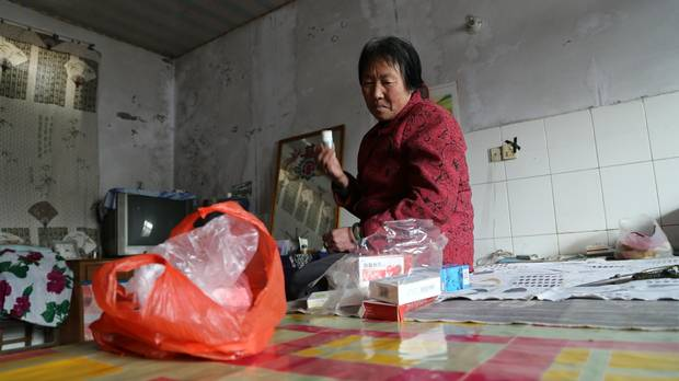Pi Fengqin, a resident of Songting, sorts through some of the medication she takes for heart and brain ailments she says have grown worse in the smog.